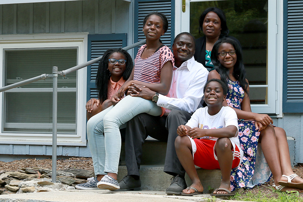 . Lawrence Nfor talks about coming to America from Cameroon and his family at his home in Leominster on Thursday night. Sitting with him on his front steps is his family. From left is Grace, 11, Helga, 13, his wife Elizabeth, Lois, 14, and Philip 9. SENTINEL & ENTERPRISE/JOHN LOVE