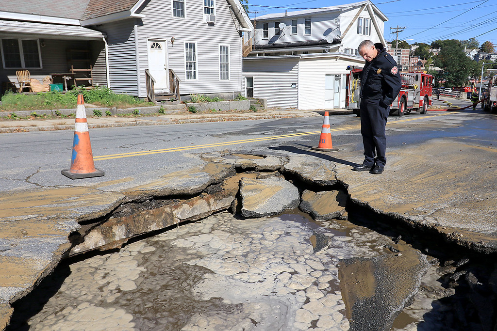 . As the Fitchburg Fire Department battled a fire at 114 and 116 Laurel Street a water main broke and water started rushing down the street. Fire Chief Kevin Roy looks into the hole now in the street caused by the water main brake. SENTINEL & ENTERPRISE/JOHN LOVE