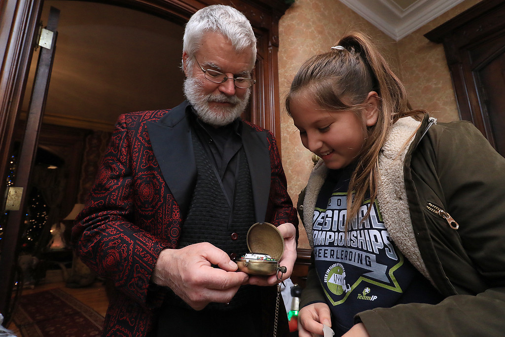 . Jack Hoover opened his home again this year for the annual Toys for Tots fundraiser he has put on for 11 years. Hoover shows Mia Rendon his pocket watch that played Christmas music and spun with two trains on it. SENTINEL & ENTERPRISE/JOHN LOVE