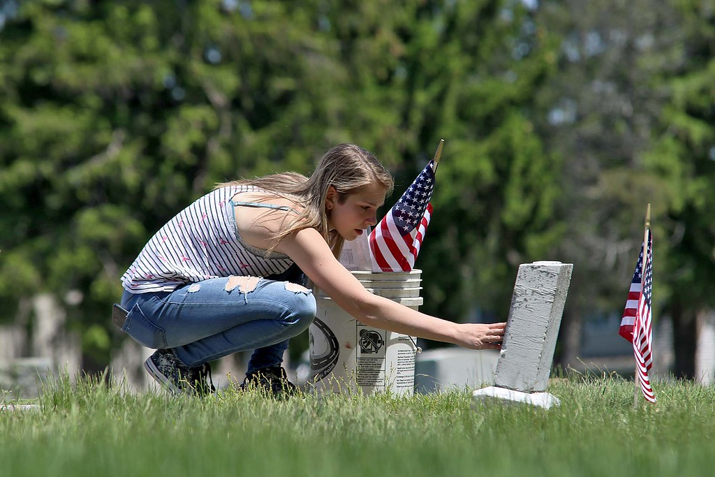 . Montachusett Regional Vocational Technical School Marine Corps JROTC Cadet Keira Henderson puts a flag on a veterans graves at Forest Hill Cemetery in Fitchburg on Thursday morning for Memorial Day. SENTINEL & ENTERPRISE/JOHN LOVE