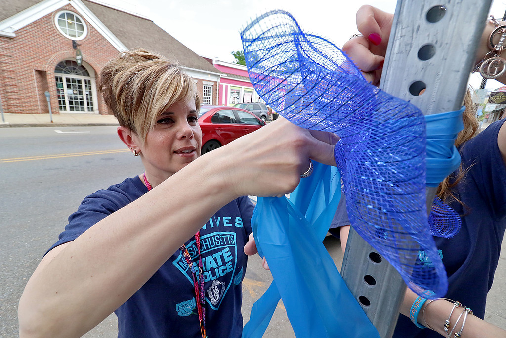 . Massachusetts State Police Wives hung some blue ribbons in downtown Leominster on Thursday afternoon. Putting up a ribbon on Central Street is Vice President of MSP Wives Debra Hall. SENTINEL & ENTERPRISE/JOHN LOVE