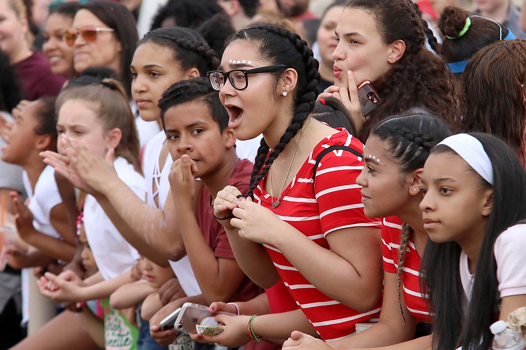 . 104th running of the Junior-Senior Relays were held at Crocker Field in Fitchburg, May 17, 2018. Cheering on her clasmates from Longsjo Middle School that were running in the relays is sixth grader Ivanny Reynoso, in stripped shirt. SENTINEL & ENTERPRISE/JOHN LOVE