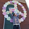 Wil Darcangelo and members of the Tribe where spreading peace and joy after erecting the new peace symbol at the First Parish Unitarian Church in Fitchburg at the top of the Upper Common. Alex Hutchings, 22, holds a sign with one of their messages in front of the new peace sign. Their idea was to help start a conversation of meaningful thoughts. SENTINEL & ENTERPRISE/JOHN LOVE