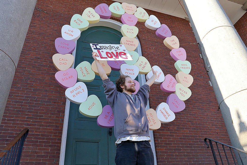 . Wil Darcangelo and members of the Tribe where spreading peace and joy after erecting the new peace symbol at the First Parish Unitarian Church in Fitchburg at the top of the Upper Common. Alex Hutchings, 22, holds a sign with one of their messages in front of the new peace sign. Their idea was to help start a conversation of meaningful thoughts. SENTINEL & ENTERPRISE/JOHN LOVE