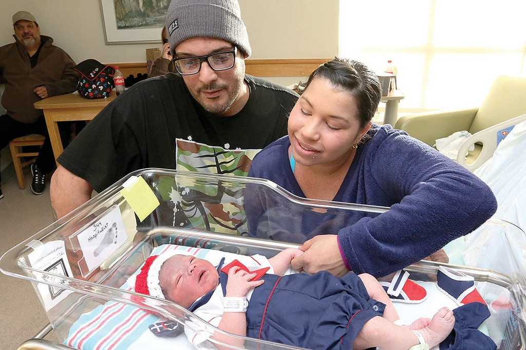 . Jennifer Rodriguez and Jamie Sepulveda-Bodon look over their son Jerremy Speulveda-Bodon who was the first baby born at HealthAlliance Hospital in Leominster at 9:06 a.m. on January 1, 2018. SENTINEL & ENTERPRISE/JOHN LOVE