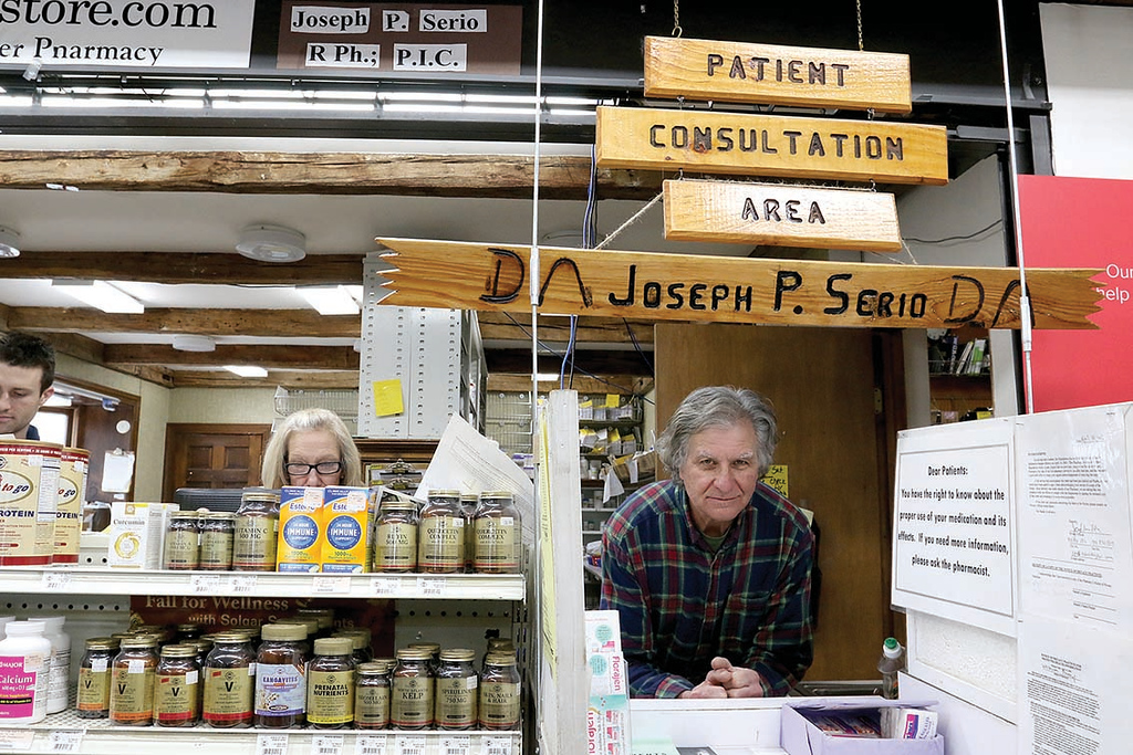 . Joe Serio, the owner of Westminster Pharmacy, one of the few remaining indepedendent pharmacies talks about his shop on Thursday morning. While talking about his pharmacy he sowed off the barn next door were he wants to sell fruits and vegetables. This wooden sign sits above the counter at the pharmacy. SENTINEL & ENTERPRISE/JOHN LOVE