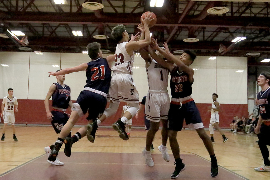 . North Middlesex Regional High School basketball played Fitchburg High School on Thursday in Fitchburg, December 20, 2018. NMRHS\'s Zach Reeves and Dominic Yancy, on left, go up for a rebound with FHS\'s Jomar Davila and Devin Deleon (#1). SENTINEL & ENTERPRISE/JOHN LOVE