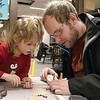 Octavia Feeley, 5, and her dad Corey Feeley of Westminster work on building and painting a wooden plane at a program put on by Robert Leduc of Wooden Toys and Crafts at the Stevens Memorial Library in Ashburnham. SENTINEL & ENTERPRISE/JOHN LOVE