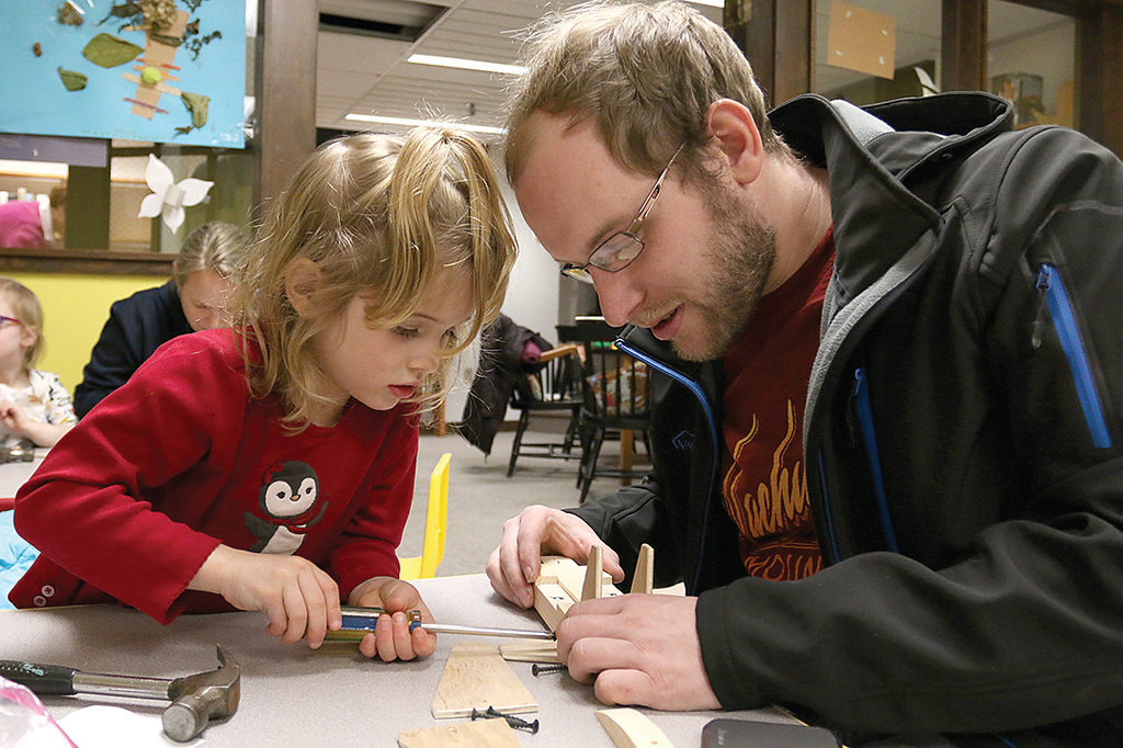 . Octavia Feeley, 5, and her dad Corey Feeley of Westminster work on building and painting a wooden plane at a program put on by Robert Leduc of Wooden Toys and Crafts at the Stevens Memorial Library in Ashburnham. SENTINEL & ENTERPRISE/JOHN LOVE