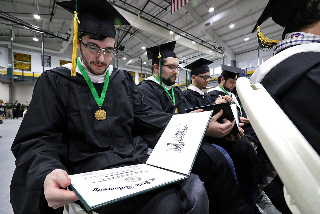 . The 122nd annual Fitchburg State University Commencement was held on Saturday, May 19, 2018 in the university\'s Recreation Center. Nathan Sidney Goldman from Leominster checks out his diplomas at the ceremony. SENTINEL & ENTERPRISE/JOHN LOVE