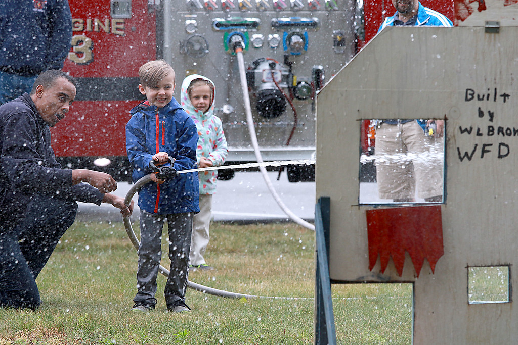 . Ruth Normandin, 6, watches as her brother Josiah Normandin, 8, shots the Ashburnham fire hose with the help of Firefighter Alex Edman at the annual Ashburnham Community Day on Saturday, June 23, 2018. SENTINEL & ENTERPRISE/JOHN LOVE