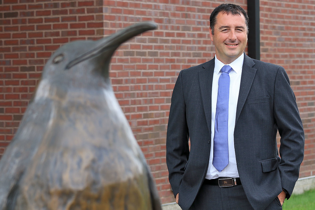 . Cushing Academy\'s new Head of School Randy Bertin stands near the statue of the school\'s mascot Pete the Penguin. SENTINEL & ENTERPRISE/JOHN LOVE