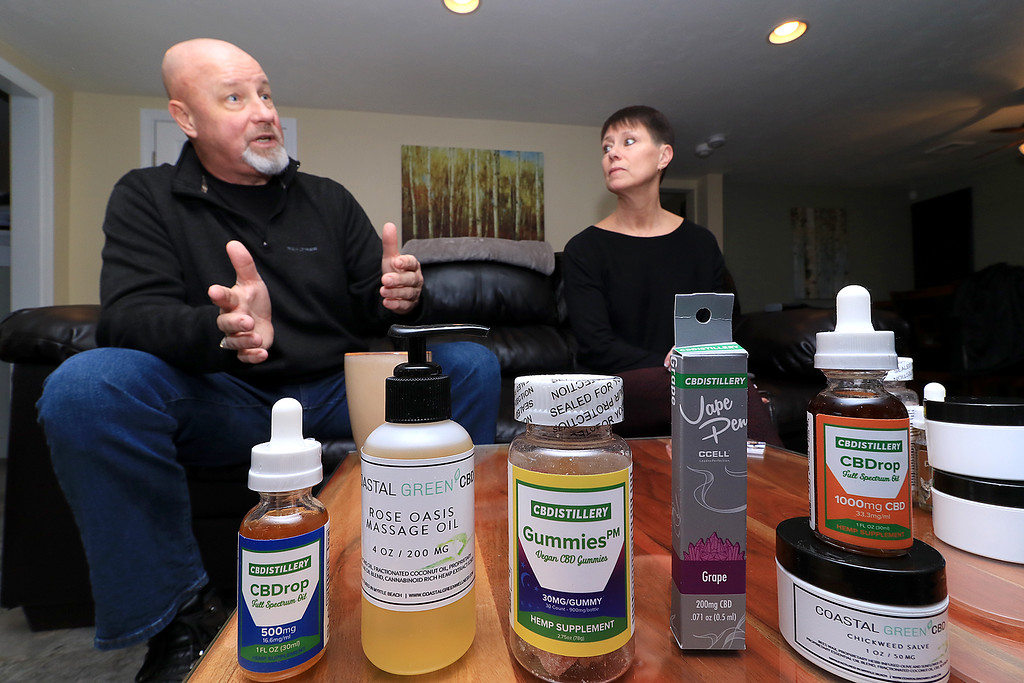 . Tim and Kim Swart of Westminster talk about there new on online store that sells CBD products. Some of their products sit on the table in front of them while they talk. From left is CBD drops, CBD rose oasis massage oil, CBD Gummies, a vaping pen some more CBD drops and some CBD salve. SENTINEL & ENTERPRISE/JOHN LOVE