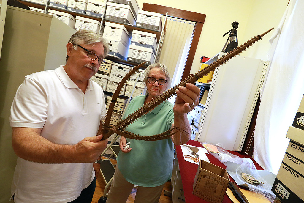 . Leominster Historical Society Trustees Mark Bodanza and Linda Pinder show off some of the weird stuff they have in storage at their building on School Street. They were not sure what this item was or what it was used for. SENTINEL & ENTERPRISE/JOHN LOVE