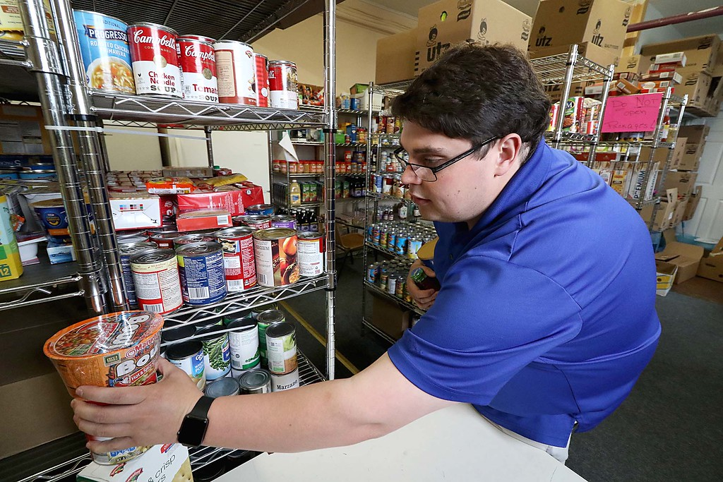 . Assistant Manager for Ginny\'s Helping Hand, Inc. Brandon Robbins sorts some of the 2,400 pounds of food they collected over the weekend during their food drive. SENTINEL & ENTERPRISE/JOHNLOVE