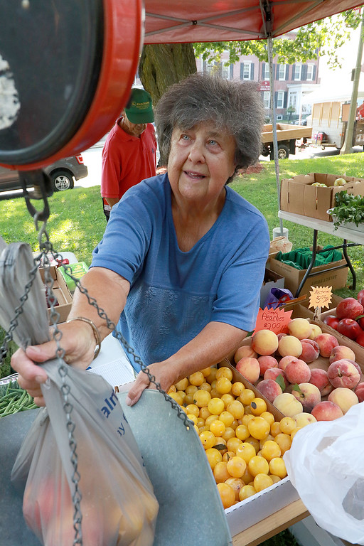 . Weighting a customers produce at the Fitchburg farmers market on the upper common on Thursday is Linda DellaMonaca with Della Farms in Lunenburg. SENTINEL & ENTERPRISE/JOHN LOVE