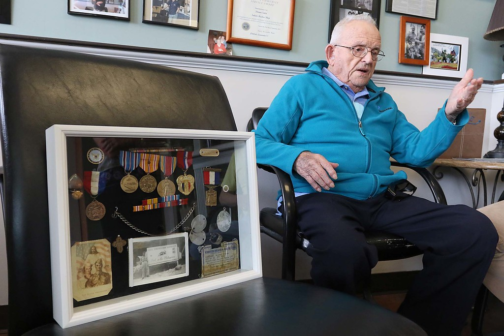 . Roland Martineau, 94, will be finally getting his high school diploma this spring, thanks to the help of his barber Donna Salvi and Bobby Penning. A shadow box of metals, dog tags and pictures of Marineau during his time in the Navy during WWII sits next to him while he talks about getting his high school diploma. SENTINEL & ENTERPRISE/JOHN LOVE