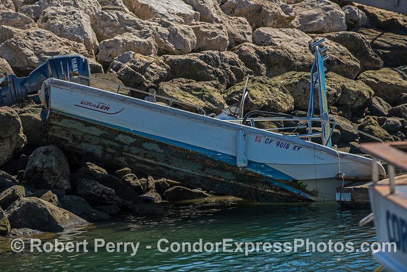 Boston whaler on the rocks - not securely tied down when the winds came