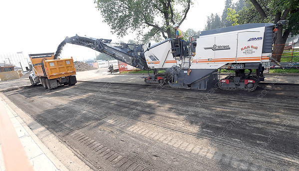A milling machine grinds down the asphalt in front of City Hall Thursday afternoon. The area around City Hall is a bee hive of activity with the new housing development down town.  July 26 2018