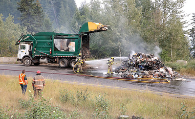 Prince George fire crews dig for hotspots in smoldering garbage after a garbage truck caught fire on Thursday evening on the North Nechako Road on-ramp leading to the Hart Highway. Citizen Photo by James Doyle       August 23. 2018