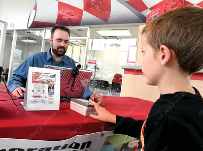 Levi Allan uses the Opweration Kidsafe program to finger print and photograph Zachary Standeven, 9, at Wood Wheaton Honda Friday morning. Wood Whaeaton Honda held the grand opening of Year-Round Child Safety Centre insinde the dealership. Citizen photo by Brent Braaten       Aug 24 2018
