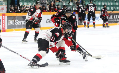 Team Black forward Arjun Atwal toe-drags the puck around the check of Team White forward Connor Bowie on Wednesday night at CN Centre during the Prince George Cougars Black vs White game. Citizen Photo by James Doyle      August 29, 2018