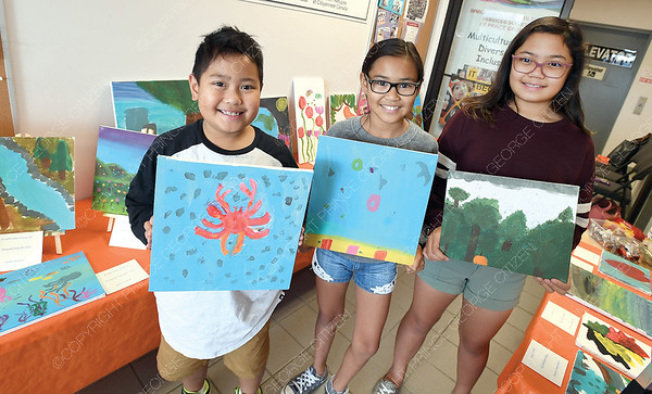 "Joshua Cabilao, 8, Aivrielle Caban, 10, and Hannah Cabilao, 12, with their art exhibit inside of IMSS. They are using the show ""strength for Today and Bright Hope for Rebuilding"" to raise funds for rebuilding Telegraph Creek. The paintings are their interpition of the world around them. Aug 29 2018"
