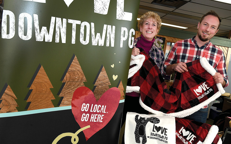 """Colleen Van Mook, Executive Director of Downtown Prince George and Eoin Foley president of Downtown Prince George get their plaid on for Plaid Friday. The event is organized by Downtown Prince George and Love Doowntown PG. The name Plaid Friday was conceived from the idea of weaving the individual threads of small businesses together to create a strong fabric that celebrates the diversity and creativity of independent businesses. This a relaxing and enjoyable alternative to the big box store """"Black Friday,"""" and is designed to promote both local and independently owned businesses during the holiday shopping season.Shop local this Friday and get into the holiday spirit. You will find the Cantata Singers strolling the downtown streets and performing festive carols. The Hubspace will become Plaid Friday Headquarters with kids' crafts, photos with Santa and even FREE giveaways. Come down early and you could take home a new shovel or some of the coveted Love Downtown PG swag (pictured). All you need to do is shop downtown anytime on Friday November 23rd and bring in your receipts between 4pm an 8pm. Santa will be available for photos from 5pm to 6pm and 7pm to 8pm. With over 30 downtown businesses participating this year, you can do your holiday shopping up until 8pm on Friday. Citizen photo by Brent Braaten"""