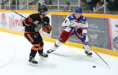 Prince George Spruce Kings defenceman Dylan Anhorn looks to make a play with the puck before absorbing a hit from Trail Smoke Eaters forward Owen Ozar on Wednesday night at Rolling Mix Concrete Arena. Citizen Photo by James Doyle       November 21, 2018