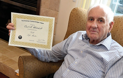 Carl Mitchell holds up his certificate for achieving Gold Life Master in The American Contact Bridge League. for Senior Scene column.