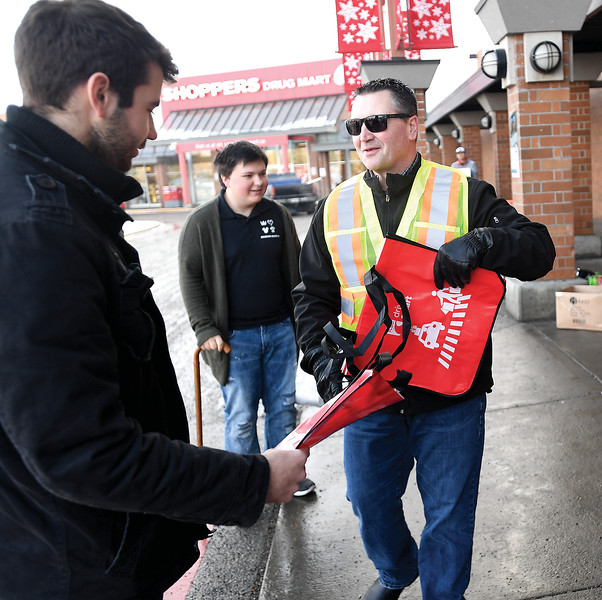 Frank Marton, centre, with ICBC talks to shoppers about driving safety in parking lots and handing out reusable shopping bags in front of Pine Centre Mall Friday over the lunch hour. December is the peak month for parking lot collisions. Citizen photo by Brent Braaten