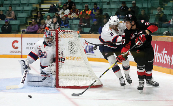 Prince George Cougars forward Mike McLean throws the puck in front of Regina Pats goaltender Max Paddock while fighting off a check from Pats defender Aaron Hyman on Friday night at CN Centre. Citizen Photo by James Doyle       November 23, 2018