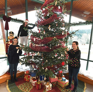 Alyssa Tobin,left, Tracy Calogheros, centre and Lisa Connor from The Exploration Place place donated ornaments on the Community Heritage Tree inside the museum Thursday afternoon. The tree features ornaments that have been donated  by the community. They are accepting more donations this year from the public that will be kept in the permanent collection. This Sunday from 11am-2pm the museum will host the members Christmas party.  Citizen photo by Brent Braaten