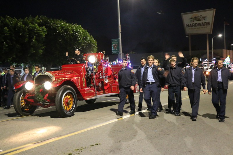 North County Fire Protection District fire explorers walk with the antique Fallbrook Fire Dept. entry in the Fallbrook Christmas Parade.  Sydney Sharkey-McFarlin photo
