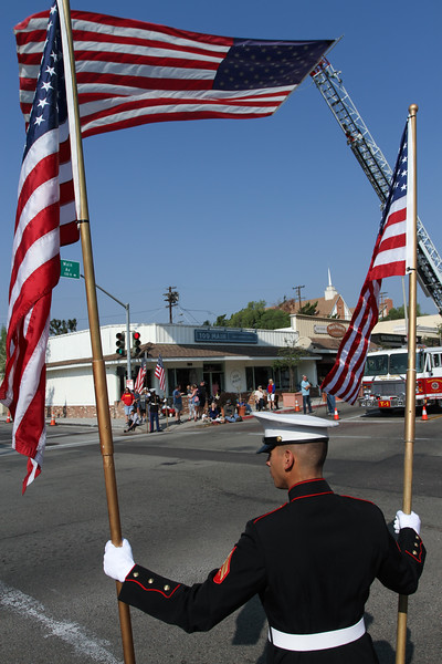 A Marine holds American flags along Main Ave in downtown Fallbrook during the annual Veterans Day Parade.