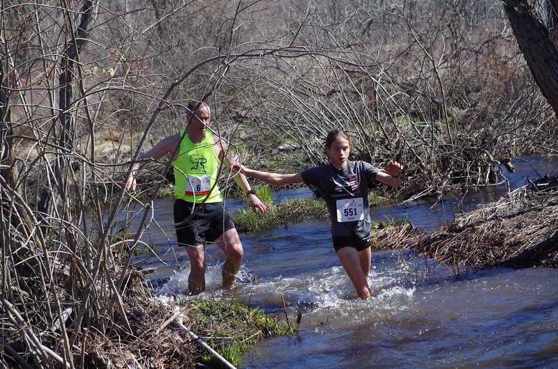 "Women's winner Kelsey Crawford at the final water crossing (aka ""Splashdown""). (Photo by Michael Rogers)"