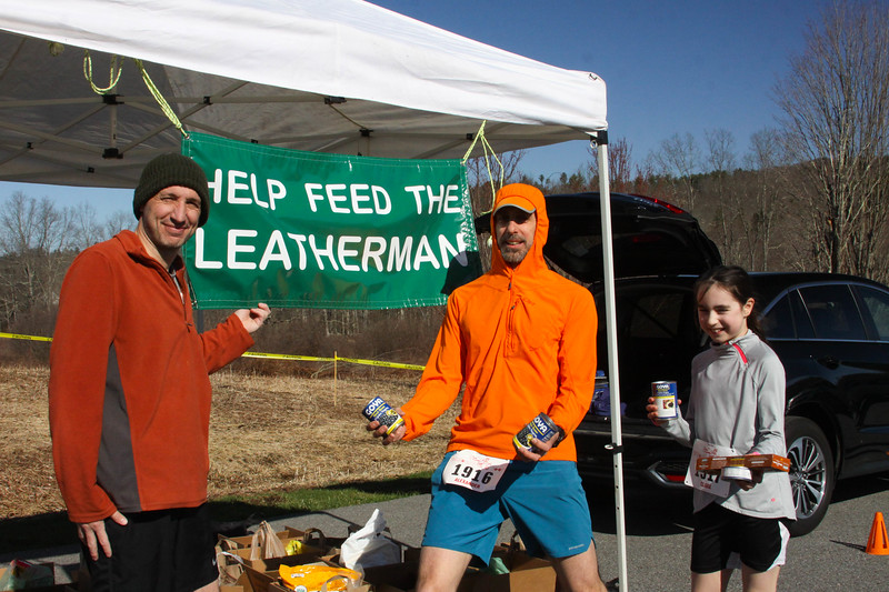 "David Ceisler accepts ""Help Feed The Leatherman"" food pantry donations for the Community Center of Northern Westchester from runners Alexander and Clara Tripp. The food drive at the loop is in its tenth year. (Photo by Bram Wegener)"
