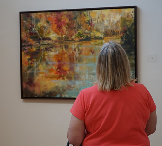 Joyce Boyette enjoying one of the oil paintings from the art gallery.