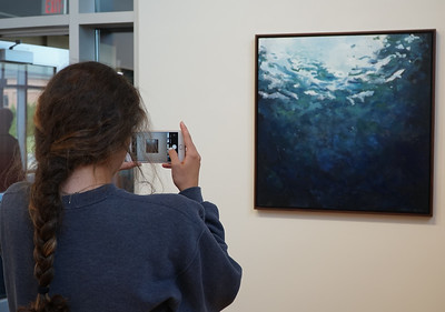 Freshman Taylor Robinson taking a photo of a painting in the gallery.