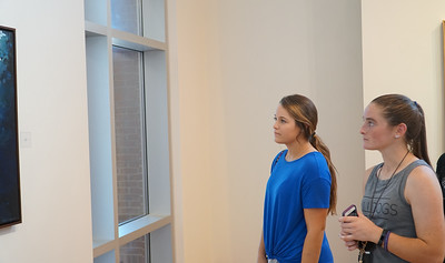 Reah Badger (left) and Abbey Goodrum (right) observe a painting.