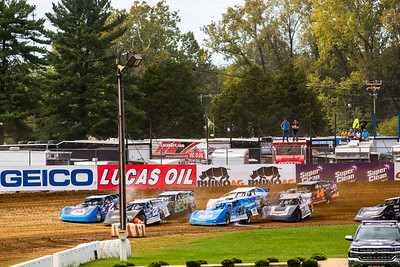Cars take off in front of Lucas Oil Late Model Dirt Series catch fence banners