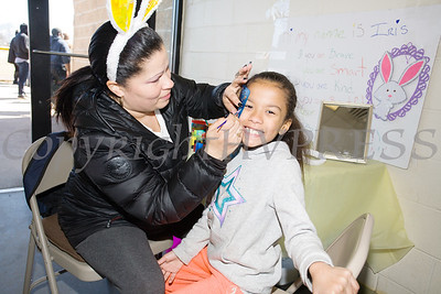 Iris Florentino paints Maria'a face as We Are Newburgh and the City of Newburgh held the Annual Easter Egg Hunt at the Activity Center on Saturday, March 24, 2018. Hudson Valley Press/CHUCK STEWART, JR.