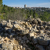 The ancient ruins of a stone structure, possibly a house, with 21st century West Jerusalem growing in the background