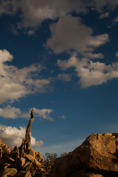 Kelsey stands high atop the Aiguille de Joshua Tree as the sun settles into the horizon.