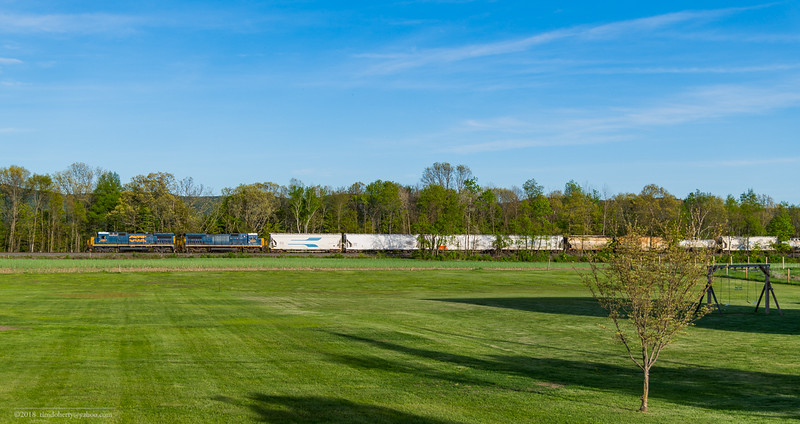 All about the across the field shots on the Conn River. Pan Am's East Deerfield to Bellows Falls train EDBF is approching the River Road Grade Crossing in Northfield.