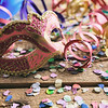 Carnival party. Mask, confetti and serpentines on wooden background