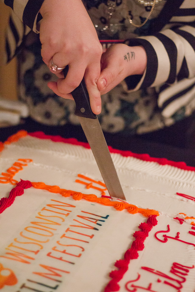 During 2018 First Look at the Fest, WFF Operations Coordinator Mallory Murphy cuts a cake celebrating the Festival's twenty years of operation.