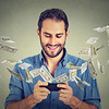 46737876 - technology online banking money transfer, e-commerce concept. happy young man using smartphone with dollar bills flying away from screen isolated on gray wall office background.
