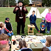 Hermann Stipp (center) explains to Woodbury Elementary School third-graders the kinds of supplies and foods a soldier in the Civil War would use and eat during the 10th Illinois Infantry Re-enactment Group's living history encampment at Knights Park in Sandwich on Friday. Students learned how to make salt pork and learned what passed for toilet paper in the Civil War.