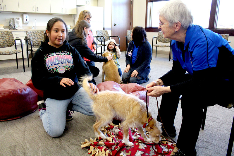 "Isela Hernandez (left) thought that the dogs from the Fox Valley Therapy Dog Club were ""pretty cool"" after seeing them for the first time at the Sandwich Public Library on April 17. The club members take their trained dogs around to different community and medical groups, to provide comfort and smiles to guests and patients."
